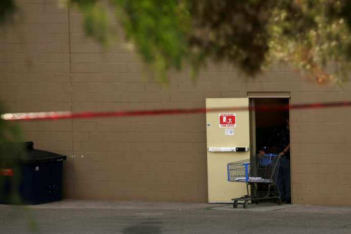 A supermarket trolley is seen behind a police cordon after a mass shooting at a Walmart in El Paso