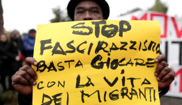 "A demonstrator holds a banner reading ""Stop fascism and racism: stop playing with migrants' life"" during an anti-racism rally in Macerata"