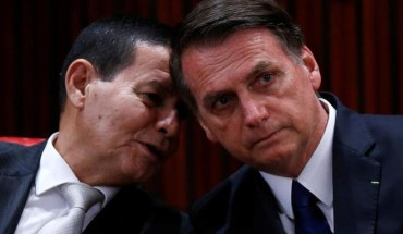 Brazil's President-elect Jair Bolsonaro listens to his Vice President-elect Hamilton Mourao before receiving a confirmation of his victory in the recent presidential election in Brasilia